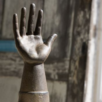 Metal statue of hand against wooden background.