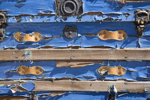 Peeling blue paint on old storage trunk.