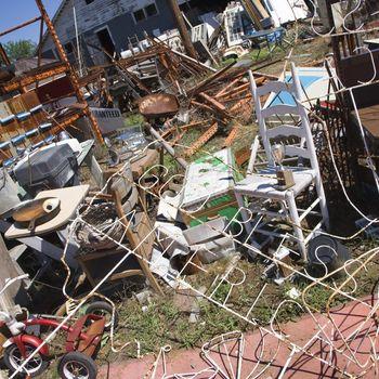 Chaotic mess of junk strewn across junkyard outdoors.