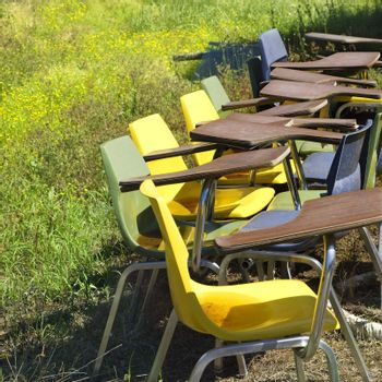Old school chairs in grassy field.