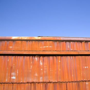 Metal orange siding and blue sky.