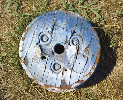 Old round wooden cog lying on ground.