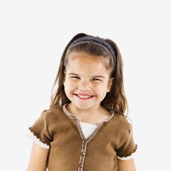 Cute little hispanic girl standing smiling.