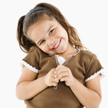 Cute little hispanic girl standing smiling at viewer.