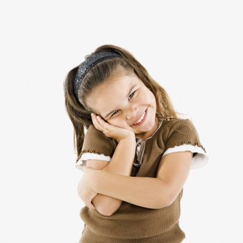 Adorable little hispanic girl standing smiling with cheek in hand.