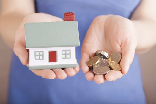 Little house toy and money in woman's hands