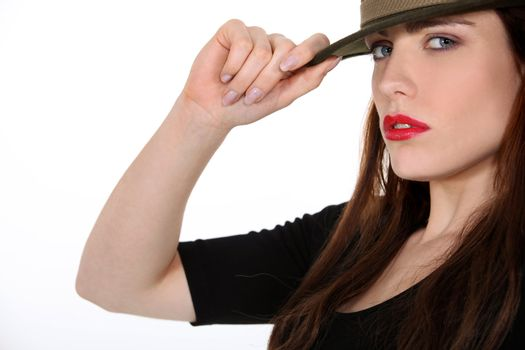 portrait of sexy brunette with hat holding a brim