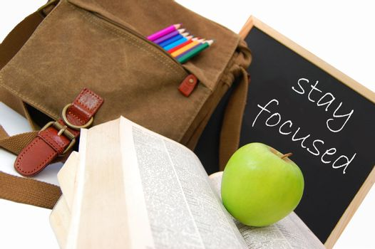Satchel and books next to a blackboard with the words stay focused