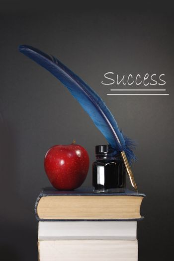 Stack of books and an apple next to a blank blackboard