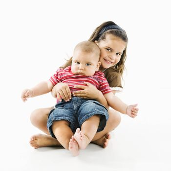 Cute little hispanic girl holding baby brother in her lap.
