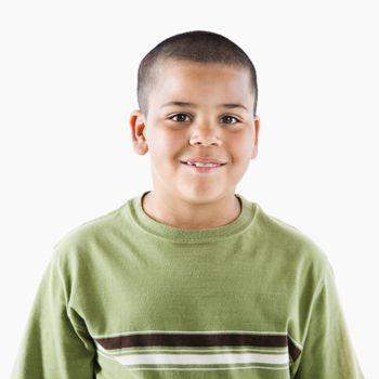 Young latino adolescent boy standing smiling at viewer.