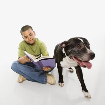 Young hispanic boy reading book while his dog sits nearby.