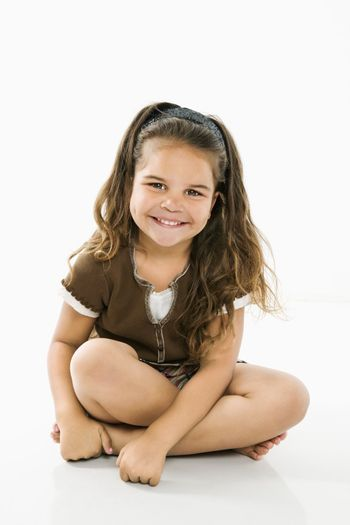 Cute little latino girl sitting looking at viewer smiling.