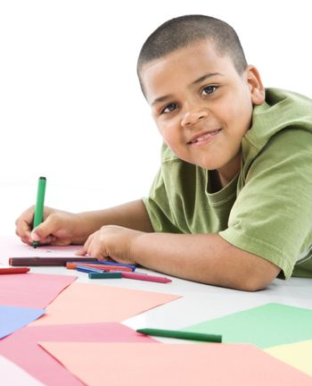 Young latino boy coloring on construction paper.