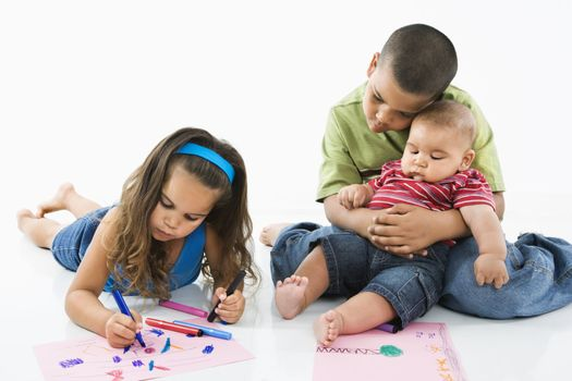 Young latino girl coloring on construction paper while brothers watch.