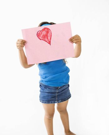 Young girl showing off drawing of heart.