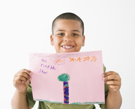 Young boy proudly showing drawing.