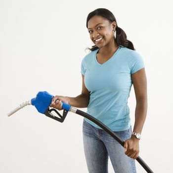 African American young adult female holding gas pump and smiling.