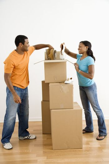 African American male and female couple packing cardboard boxes with shoes.