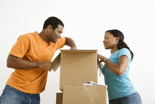 African American male and female couple packing cardboard boxes.