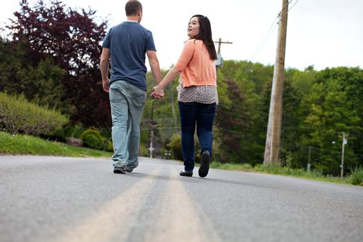 Young happy couple enjoying each others company outdoors walking down an empty road with the woman looking back at the viewer. Plenty of copy space.