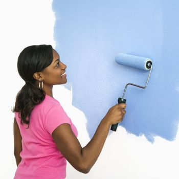 African American woman painting wall blue.