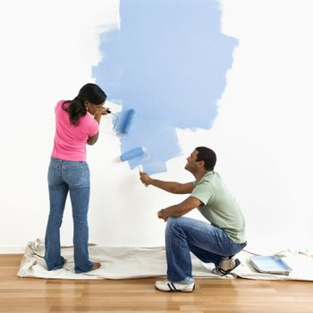 Smiling African American male and female couple painting wall blue.