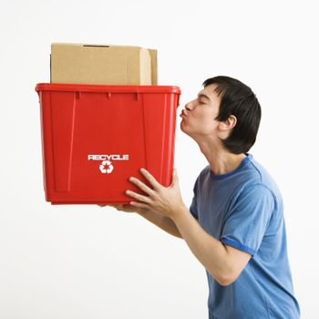 Portrait of Asian young man standing kissing recycling bin.
