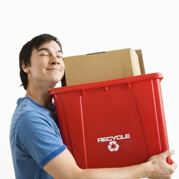 Portrait of smiling Asian young man holding recycling bin.