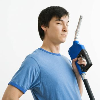 Asian young man holding gasoline pump nozzle.