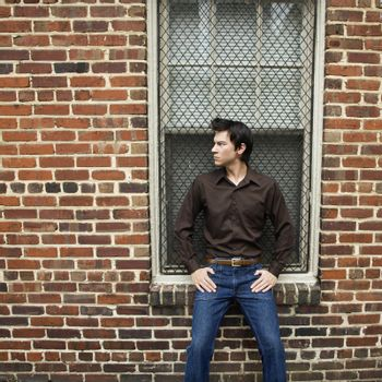 Asian man standing and leaning against window and brick wall.