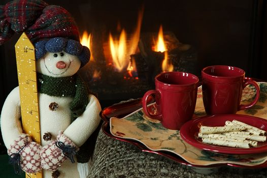 Get warm by the fire on a chilly winter day. snowman,snow,hat,gloves,mittens,scarf,fire,fireplace,logs,flames,cups,mugs,plate,cookies,snacks,warm,warmth,cozy,snack,smile,winter,chilly,emotion,heat,drinks,food,tray,seasonal,christmas,holidays,beverages,coffee,chocolate,cider,
