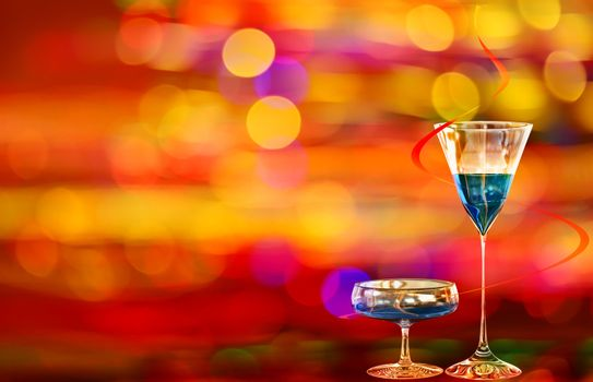 Two blue cocktails with curacao on the background with various colors of illumination of the night city