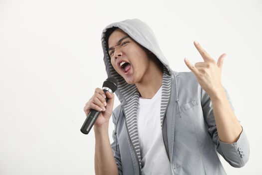 man holding microphone with the hand sign
