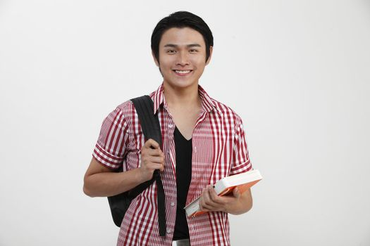 Young man standing and holding books