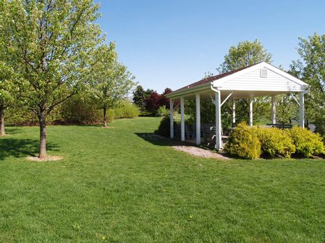 an outdoor picnic pavilion by a green lawn and trees