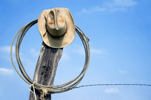 Weathered cowboy hat and lasso hanging from the leaning post of a barbed wire fence.