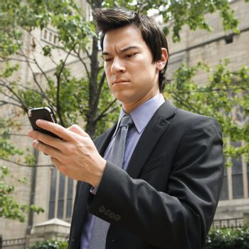 Asian business man standing looking at cell phone messages.