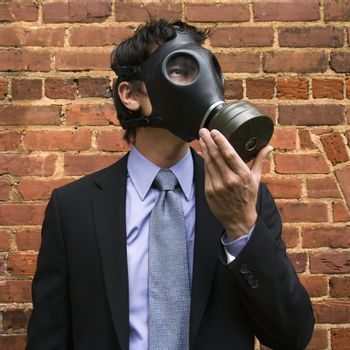 Businessman standing next to brick wall  and looking off to side wearing gas mask.