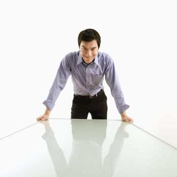 Young Asian business man standing over conference table with devilish grin.