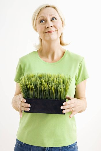 Portrait of attractive adult woman holding pot of grass and looking up.