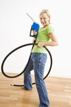 Portrait of adult blonde woman holding gas nozzle like a gun slinger.