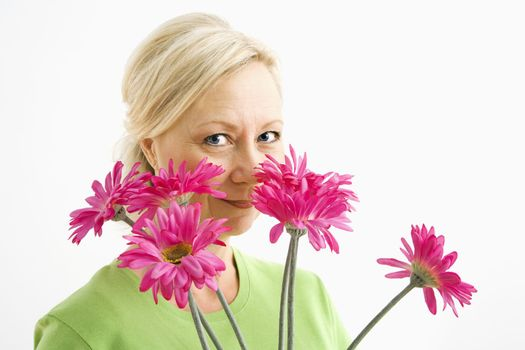 Portrait of smiling adult blonde woman looking over bouquet of pink flowers at viewer.