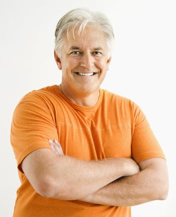 Portrait of smiling adult man standing looking at viewer with arms crossed.