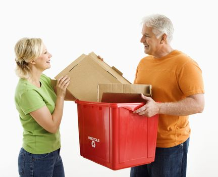 Man holding recycling bin while woman places cardboard into it.