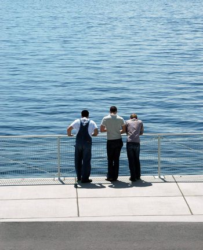Friends standing on a bridge.