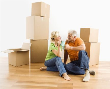 Middle-aged couple sitting on floor among cardboard moving boxes drinking coffee.