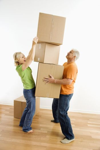 Middle-aged man holding stack of cardboard moving boxes while woman places another one on.