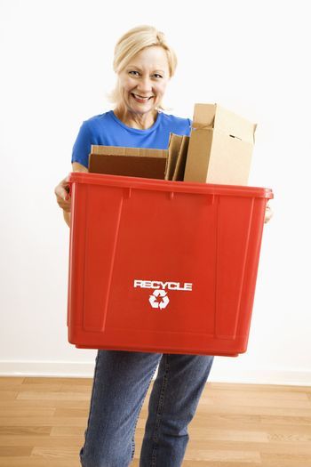 Portrait of smiling adult blonde woman holding recycling bin full of cardboard.