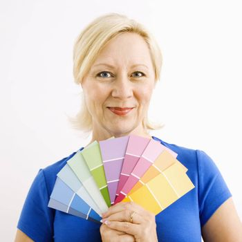 Portrait of smiling adult blonde woman holding paint swatches.
